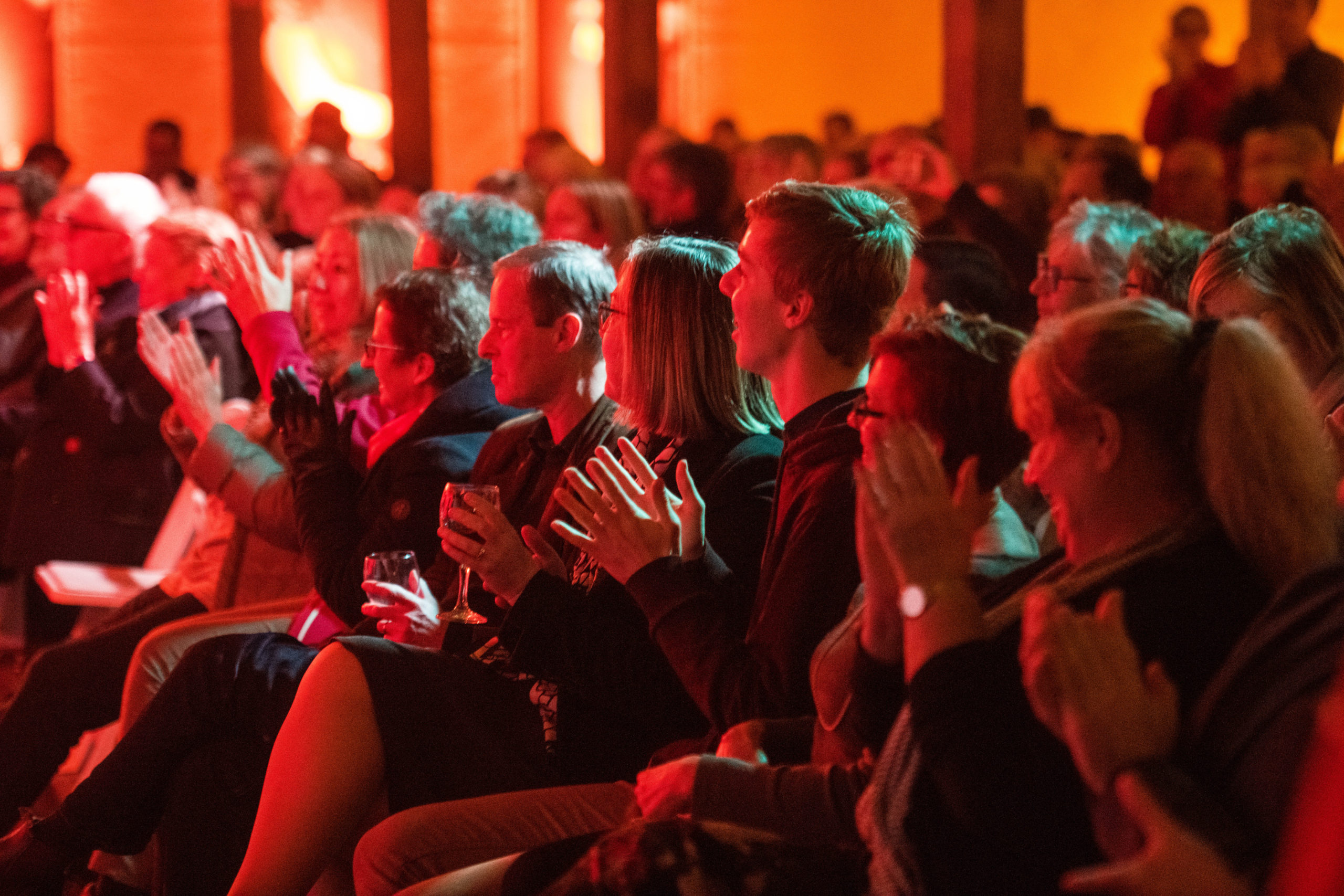 The audience watches and claps for a Festival of Voices performance in 2019, although we cannot see the performers