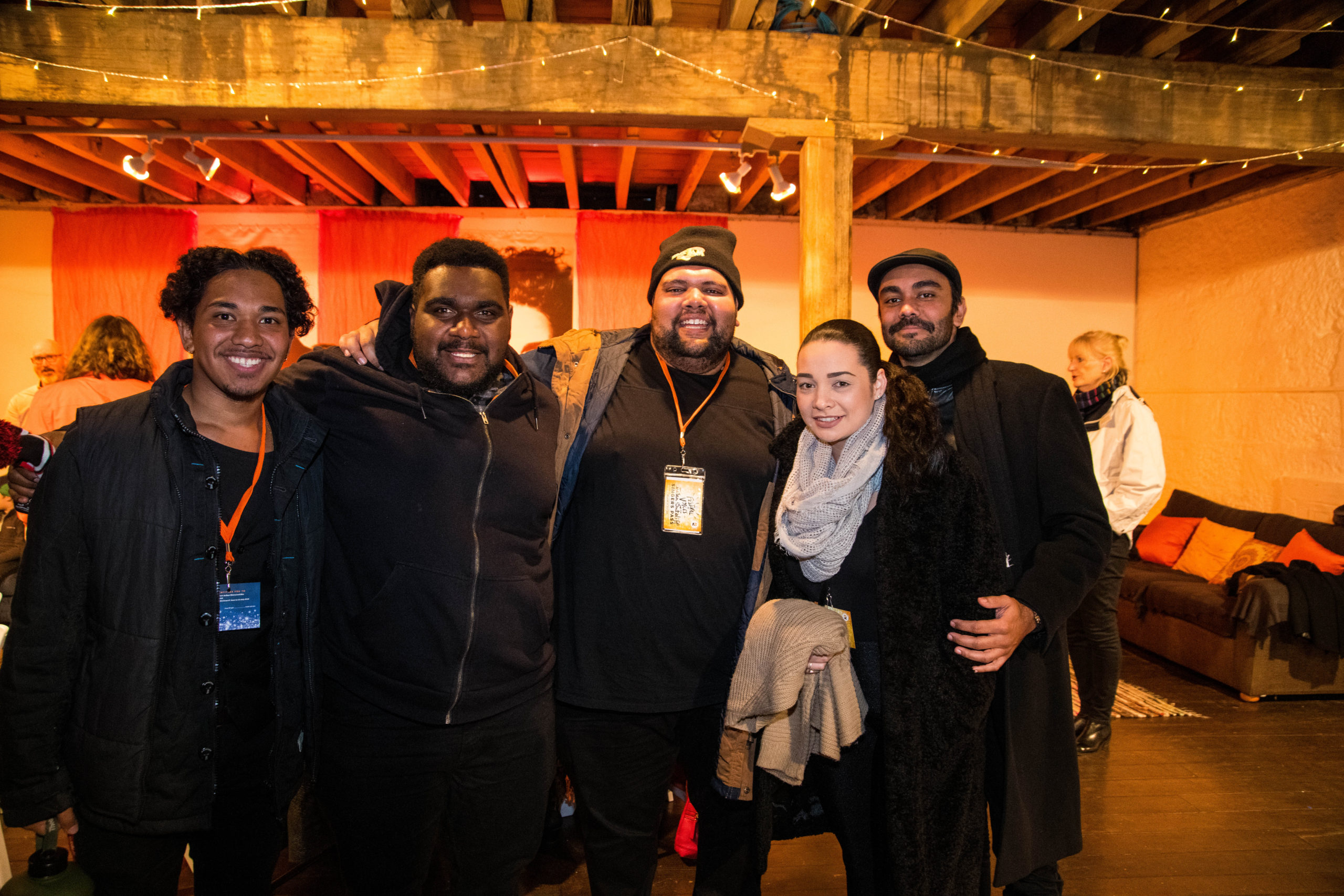 Group of 5 people wearing winter attire embracing and smiling at the camera
